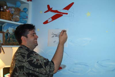 me painting a plane on the wall of my buddy's child's wall
